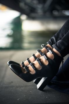 buckles. High leather heels with straps. Fashion last trend for black shoes. Original design.