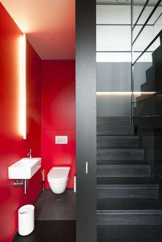 Helle Gästetoilette mit roter Wandfarbe neben futuristischem Treppenhaus