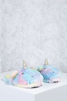 A pair of plush slippers featuring an embroidered sleeping unicorn design, a standing glitter horn and ears, and pastel colors.