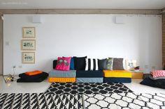 Sala com futons coloridos e composições de tapete em preto e branco.