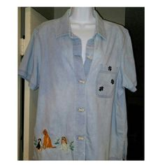 Woman's Button Down Shirt Lite Blue decorated with Dogs Flowers and Paws. 4 Dog bone button closure. The very top 1 is missing, not noticeable at all.  1 left breast pocket. Small slit on each side. Very good condition. If you love dogs this is a must. Blair Tops Button Down Shirts