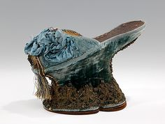 """Chopines: 1590-1610, Italian, silk, metal. """"The chopine was a tall clog worn in primarily in Venice from the 15th to the early 17th centuries...most examples... three and five inches tall, some specimens of over a foot tall survive... accounts testify to the necessity of the assistance of a pair of ladies maids to walk... the purpose of the chopine was as much to elevate the lady's sartorial reputation as to elevate her skirt from the dirt of the streets and to increase her physical…"""