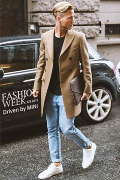 Try pairing a camel overcoat with light blue skinny jeans to create a dressy but not too dressy look. Dress it down with white low top sneakers. Shop this look for $264: http://lookastic.com/men/looks/overcoat-and-crew-neck-t-shirt-and-skinny-jeans-and-low-top-sneakers-and-zip-pouch/4005 — Camel Overcoat — Black Crew-neck T-shirt — Light Blue Skinny Jeans — White Low Top Sneakers — Dark Brown Leather Zip Pouch