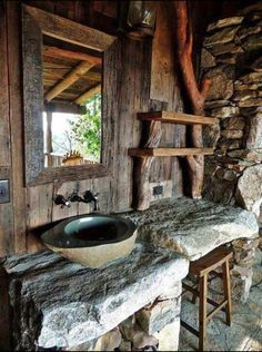 Very rustic bathroom with driftwood and stone.