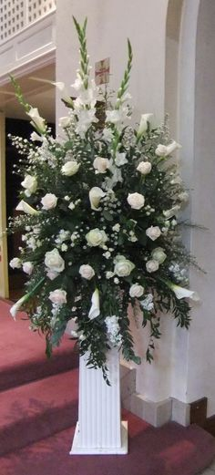 Wedding flowers from The Herb of Grace Farnham Large cream, white and green pedestal using avalanche roses, Norma Jean roses calla lilies, gladioli, aster, eucalyptus, ruscus,