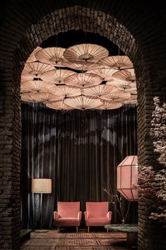 A moody and Asian style lounge design with a beautiful decorative lighting featuring a cluster of paper parasol umbrellas.