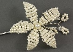 Vintage Bloom Pearl Flower Wedding Hair Grip. The Vintage Bloom hair grip is a pretty feminine hair accessory, each petal is hand beaded with small glass seed beads and the centre of the flower is completed with a pearl. The flower has been further enhanced with a small sprig of beaded leaves and swarovski bicone crystals. Available as a hair grip or hair pin. Available in a fabulous range of pearl, seedbead and crystal colours