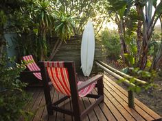 If you don't live in a tropical local, fret not, you can still create a backyard space that's so relaxing, you'll feel like you're on a Hawaiian getaway all year long. Mix lush, leafy plants, comfortable chairs and natural elements (like this drift-wood rail and bamboo fence) to bring the beach to you. Vintage or used surfboards can be purchased for bargain prices in even landlocked regions.