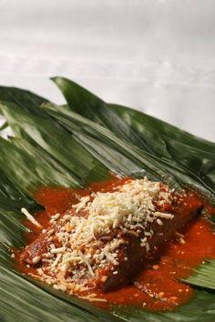 Tamal de frijol bañado con salsa de guajillo.