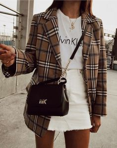 Look saia jeans branca, tshirt branca, blazer xadrez e bolsa com alça de corrente.