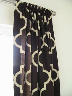 Maybe use the same pattern as the rug, but reverse the colors for the curtains.