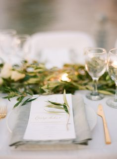 A beautiful place setting with white plates, grey linen napkins, gold flatware, and olive branches to nod to the destination, Greece.