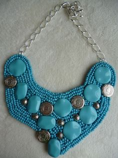 Maxi Colar confeccionado em peças de resina e miçangas na cor Azul Turquesa e peças variadas na cor prata. Acabamento em corrente de metal prata. Base em feltro na cor Azul Turquesa....