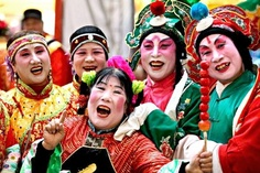 The color costumes and makeup of these Chinese dancers represent spring, renewal, hope and unity.