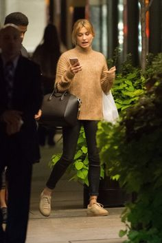 Hailey Baldwin wears a camel turtleneck sweater, skinny jeans, a Givenchy bag, and platform suede Puma sneakers