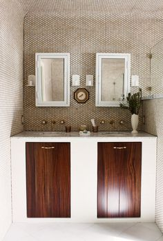 Double vanity in bathroom with tiled walls, white mirrors, and plant