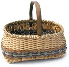"Traditional Ozark Basket  10""h x 12""l x 9.5""w     ( Tony Stubblefield) made this basket at the 2000 Missouri Basketweavers Convention in St. Louis. The workshop was taught by Arkansas native Luke Block. The basket was woven of natural, walnut dyed and color dyed white oak. The handle was made of dark walnut."