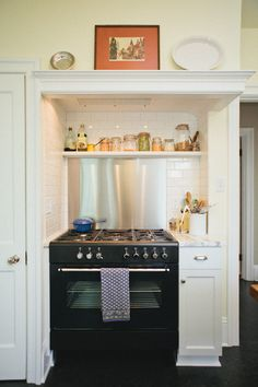 Little cooking nook.  Stainless steel backsplash...repinned not because of style, but because I like the idea of having shelves over the oven that help to give easy access to things that have to take up my already limited counterspace right now