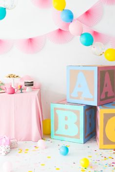 Giant baby blocks are a cute DIY decoration for a baby shower or baby's first birthday party. You just need cardboard boxes, stencils, and paint. So easy!