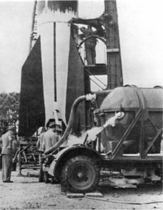 A fueling trailer shown before is filling a V2 Rocket for imminent launching.