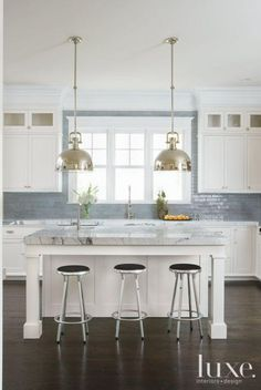 Modern meets traditional gray and white kitchen with classic shaker upper and lower cabinets, carrara marble counter tops, glossy small subway tile counter-to-ceiling backsplash, kitchen island with backless silver bar stools, and industrial farmhouse-style oversized domed silver pendant lights.