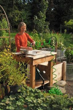 Garden Sink~ clean water comes from a self-coiling hose that's fed by a ground level hose bib under the table.  Hang the hose from the hook next to the sink when not in use.  The used water drains back into the garden.  There is a small compost bin on the left side of the table for compost from the harvest