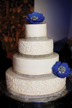 White wedding cake with bling and blue flowers