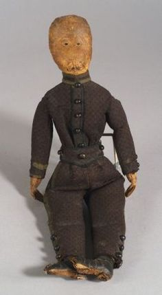 Folk Art Doll, America, 19th century, the male figure possibly wearing military clothing, the stuffed leather head with stitched facial features, hands, and feet, brown woven wool jacket and trousers with olive green and black trim, shoebutton accents, (wear, minor losses), ht. 17 in.