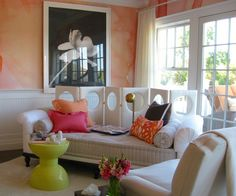 Room in Sherbert. The pops of colors (yellow, orange, etc.) and soft pink walls warm up the white furniture, trim and large windows.