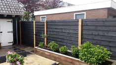 Leuke tuinafscheiding met tuinpoort van zwart geverfd Zweeds rabat en Douglas palen.
