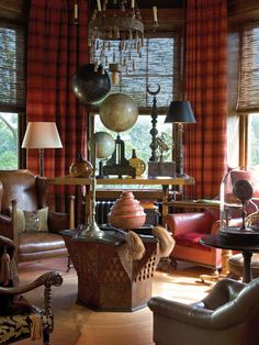 An octagonal turret expands the end of the library and is set for scholarly pursuits with antique globes. Great masculine feel here. Love the window treatments.