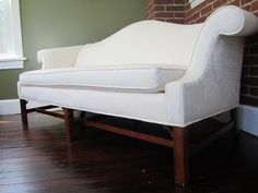 """Camel Back   A pristine Ethan Allen Camel-Back sofa, covered in a brilliant white floral print. It's classical styling is duly complimented by a rich walnut frame and sophisticated wood detailed leg. The Camel Back also includes two matching throw pillows (not pictured.)    Dimensions:  68""""L x 31""""D"""