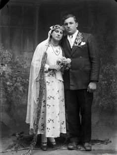 Early 20th century wedding photo.  I wish I knew where these people lived. They have interesting adornments, especially the very long thing hanging down her side. I looks like it might be beaded.