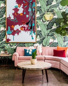 A Pink couch and palm print wallpaper (The Dwell Hotel)