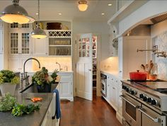 "White Kitchen Ideas. This white kitchen has so many great design ideas. Countertop is honed Pietra De Cardosa and the perimeter counters are Blizzard Caesar Stone. The stunning pendants are the Orson Pendants by Remains. Cabinet Paint Color: ""Benjamin Moore Decorators White CC-20"" #WhiteKitchen"