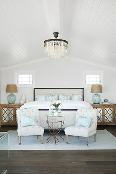 This home's designer, Becky Owens, made a cozy nook at the foot of the bed with two tufted chairs. Don't have the space? Tuck in an upholstered bench or pouf. - HouseBeautiful.com