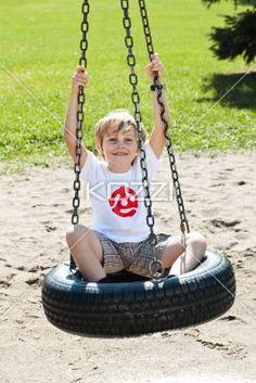 portrait of a elementary boy sitting on tire swing. - Portrait of a elementary boy sitting on tire swing in a park,