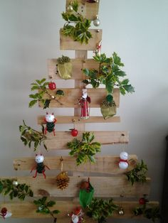 "Bits of  unused wood from pallets made a cool and rustic Christmas tree.  Mum refers to it as the Robinson Crusoe tree.  Added some home made decorations and holly from the garden.  To make it stand straight and give it a base, we screwed some of the 2"" blocks to the bottom of the tree to keep it upright."