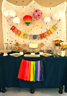 first birthday, cookies and milk, hot air balloon theme, clouds, rain, bright colors, rainbow cake