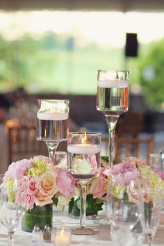 Pink and yellow flower arrangements surrounded floating candles. #WeddingDecor Photography: Vanessa Joy Photography. Read More: http://www.insideweddings.com/weddings/a-garden-inspired-summer-wedding-at-a-golf-club-in-new-jersey/631/