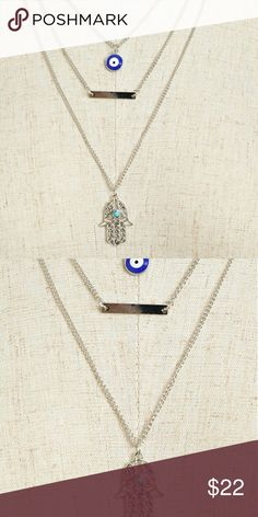 """Jewelry   SILVER HAMSA EVIL EYE BAR LAYER NECKLACE NWT brand new in original packaging // triple chain layered silver-plated necklace // blue evil eye stone, silver bar, & filigree Hamsa Palm / Hand of Fatima //  turquoise stone in center // length: 9.5"""" + extender for adjustable length // *Nickel & Lead Compliant!* // -Also available in Gold, see separate listing- // bundle & save, price firm // 3 available! Jewelry Necklaces"""