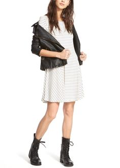 Pairing a striped shift dress with leather accessories for an edgy street style with a feminine flair.