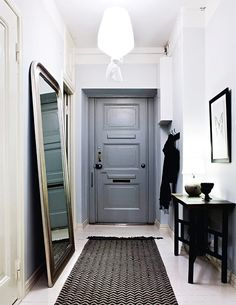 The grey front door is the eye-cather of this hall. The high space is also accentuated by a mirror leaning on the wall and the interesting lamp.