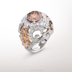 Adour Ring, Bals de Légende collection White gold, round diamonds, pink gold, pink diamonds, one 4,04-carat round fancy orange-pink diamond The Adour ring from the Bals de Légende collection is inspired by the boteh motif, a mystical Iranian flower. Symbol of love, this motif is represented in a pair of two symmetrical motifs on each side of the ring. This unique creation is adorned by an extremly rare 4,04-carat fancy orange-pink diamond with an intense color.