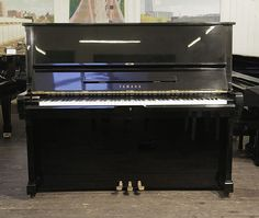 A 1973, Yamaha U2 upright piano with a black case and polyester finish at Besbrode Pianos £3500. Piano has an eighty-eight note keyboard and three pedals.