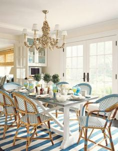 French bistro chairs in light blue and white and a  Zinc top table, work together with natural elements like the oyster shell encrusted chandelier, bamboo shades to  make this a great styled room for the Lowcountry.