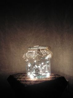 Glass jar with twinkle lights, doilies or fabric tied with twine = bottled magic, looks like fireflies in a jar
