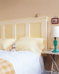 A solid old door, refinished and hung sideways, becomes a perfect- and perfectly inexpensive- headboard for a bed.