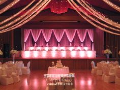Backdrop and Head Table for wedding at Glessner Auditorium - Oglebay. Backdrop included custom draping and crystal curtains. Tables decorated with our ruched table skirting. Uplighting in Warm Pink.