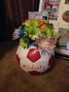 Soccer ball vase -Cut hole size of cup -Glue rocks to bottom so it doesn't roll -Stuff news paper to plump up ball... leaving room for cup -Insert plastic cup -Hot glue ring of cup to ball ao it doesnt fall out Add flowers and water Great for basketball and football too